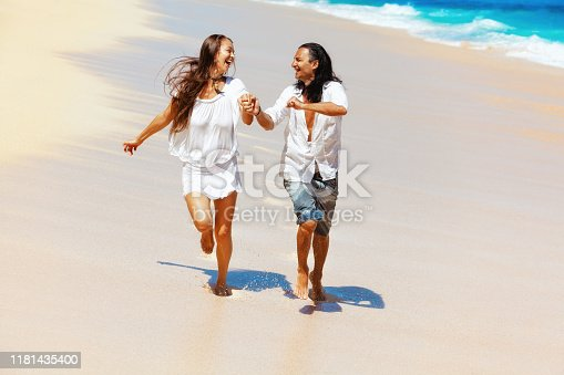 577645320 istock photo Young couple run by white sand beach along sea surf 1181435400