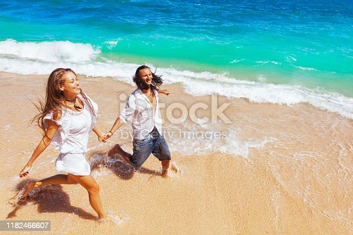 577645320 istock photo Young couple run by white sand beach along sea surf 1182466607