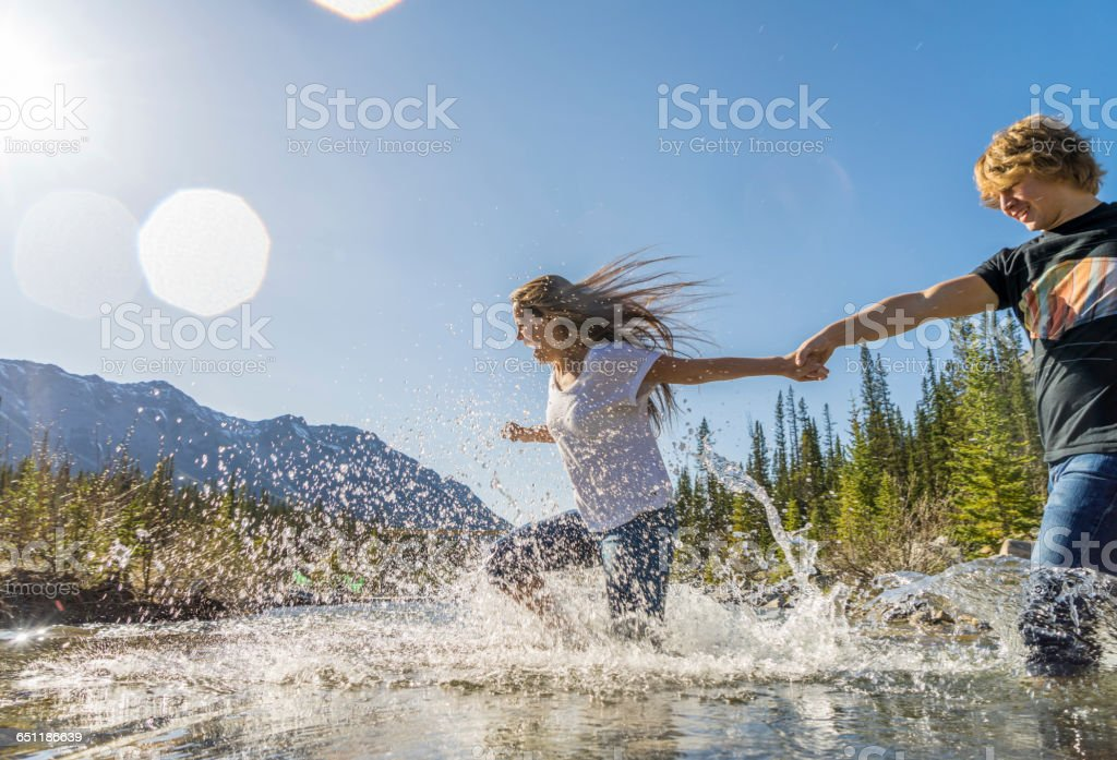 Young couple run through mountain creek together – Foto