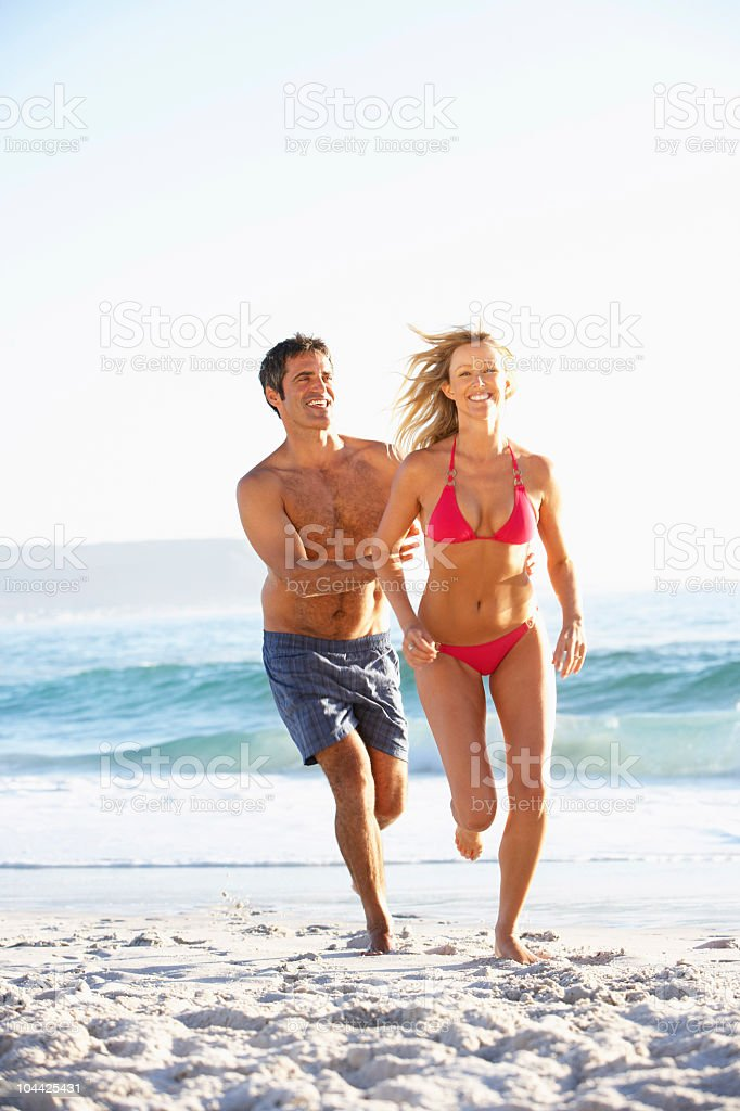 Young Couple Running Along Sandy Beach on Holiday royalty-free stock photo