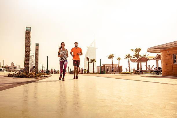 junges paar-laufen-fitness und sport in dubai - jumeirah stock-fotos und bilder