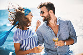 Young couple drinking white wine on the yacht and enjoying sailing.