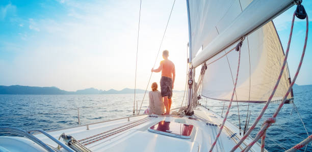 Young couple sailing in the tropical sea at sunset on their yacht stock photo