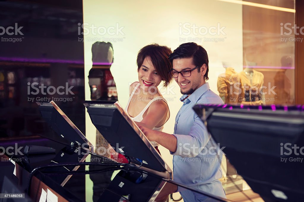 Young couple selecting a movie at the shopping center stock photo