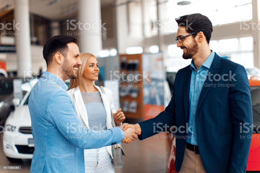 Young couple shaking hands after a successful car buying stock photo