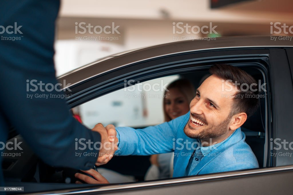Young couple shaking hands after a successful car buying - Foto stock royalty-free di Accordo d'intesa