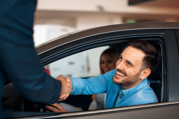 Young couple shaking hands after a successful car buying Young couple shaking hands after a successful car buying car salesperson stock pictures, royalty-free photos & images