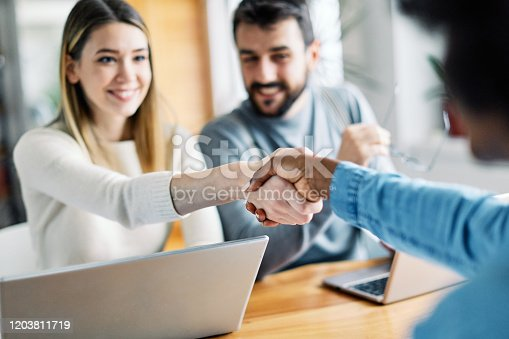 994164766 istock photo young couple shaking hands deal contract real estate investment 1203811719