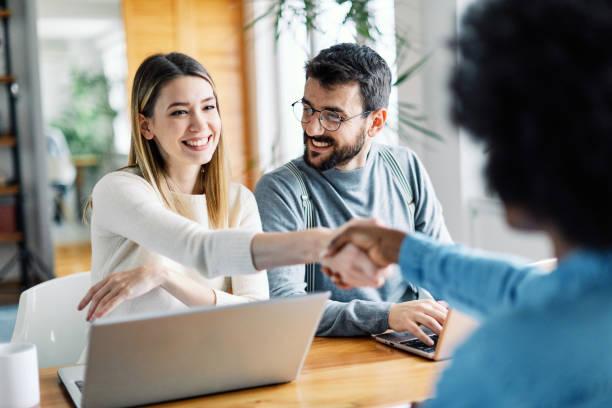 giovane coppia stringendo la mano affare investimento immobiliare - banca foto e immagini stock