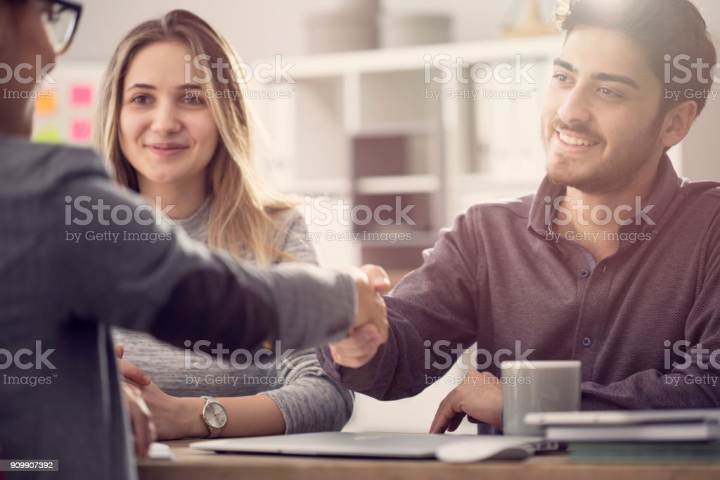 Young couple shaking hands with a female agent foto stock royalty-free