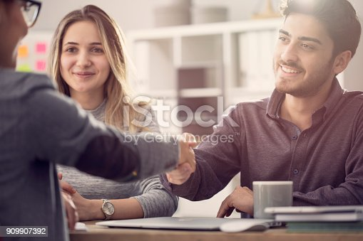 istock Young couple shaking hands with a female agent 909907392