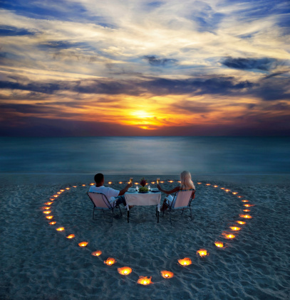 young couple share a romantic dinner with candles heart on the sea sand beach
