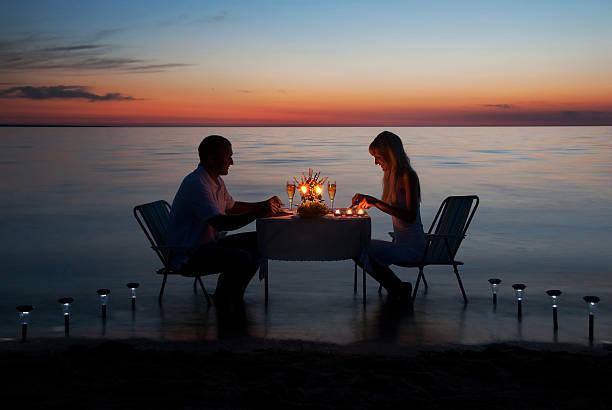 joven pareja compartir una cena romántica con velas en la playa - cena romantica fotografías e imágenes de stock