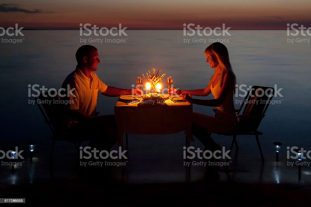 young couple share romantic dinner with candles on the beach stock photo