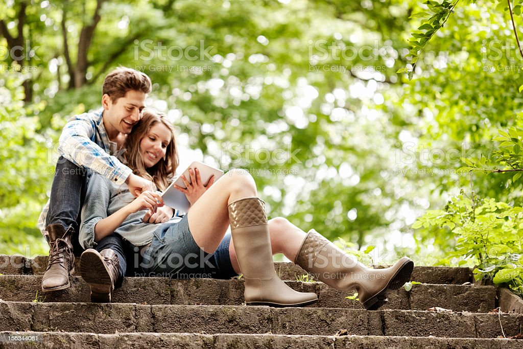 Young couple sharing a tablet computer outdoors royalty-free stock photo