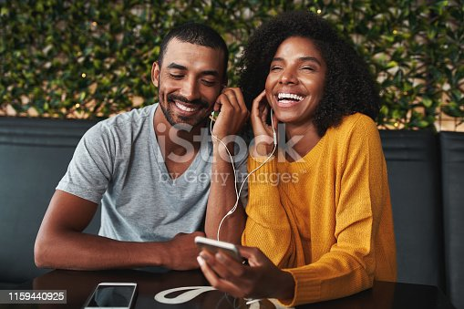 Close-up of a smiling young couple in cafe sharing one earphone and enjoying listening music on mobile phone