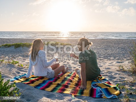 Two people sharing moment at sunset while relaxing on blanket with a glass of wine outdoors on beach