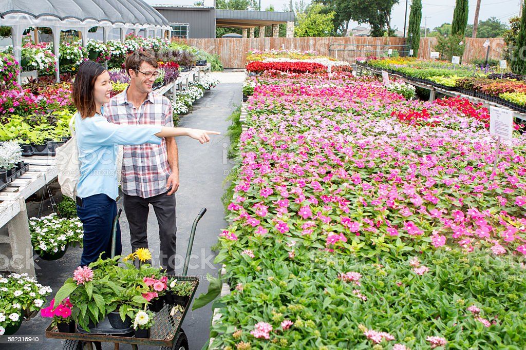 Asian woman and Caucasian man choose flowers to purchase at local...