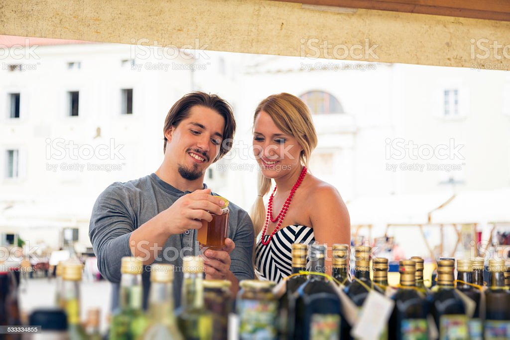 young couple shopping for olive oil stock photo