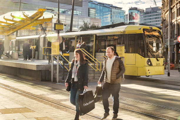 Young Couple Shopping in Manchester, UK, and Metrolink Tram stock photo