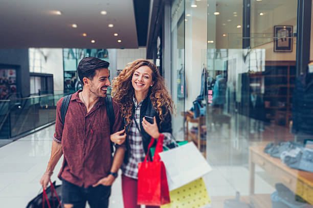 young couple shopping in the mall - shopping stock photos and pictures