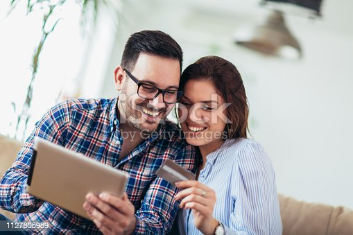 842971872 istock photo Young couple shopping on internet with tablet 1127805989