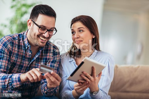 842971872 istock photo Young couple shopping on internet with tablet 1127807515