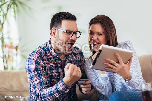 842971872 istock photo Young couple shopping on internet with tablet 1127807704