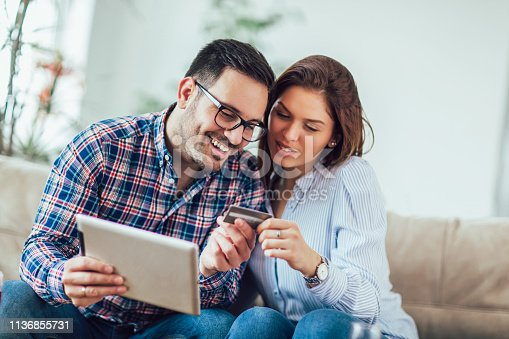 842971872 istock photo Young couple shopping on internet with tablet 1136855731