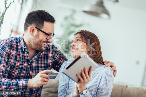842971872 istock photo Young couple shopping on internet with tablet 1136855741