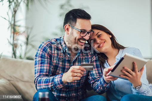 842971872 istock photo Young couple shopping on internet with tablet 1141649652