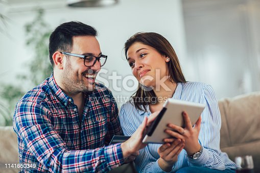 842971872 istock photo Young couple shopping on internet with tablet 1141650349