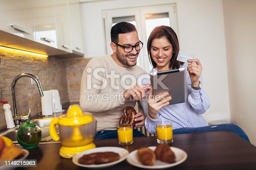 842971872 istock photo Young couple shopping on internet with tablet 1149215963
