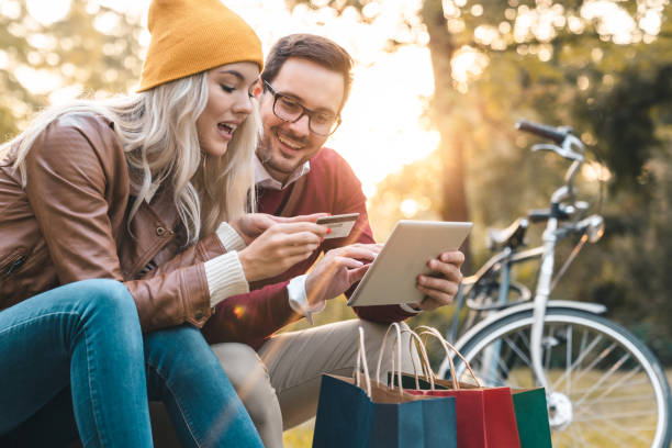 young couple shopping online with credit card on tablet in public park - spending money stock pictures, royalty-free photos & images