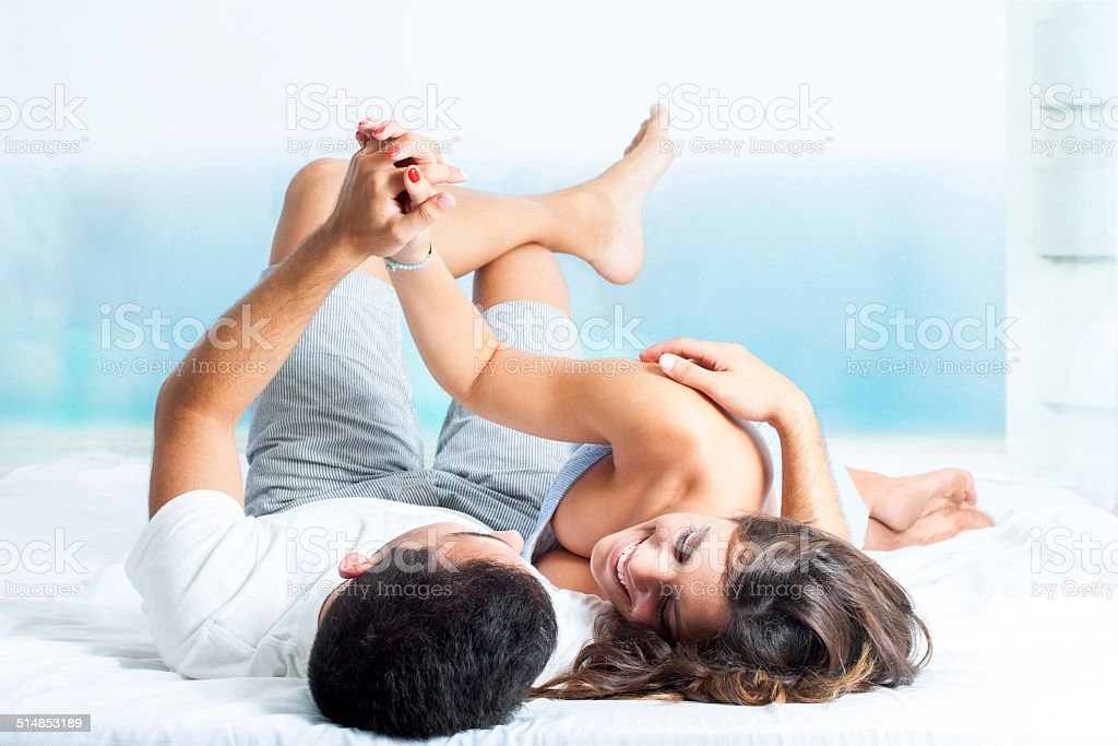 Young couple showing affection in bedroom . stock photo