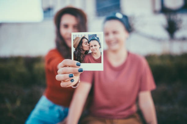 Young couple showing instant portrait to the camera Lesbian couple showing instant selfie cute teen couple stock pictures, royalty-free photos & images