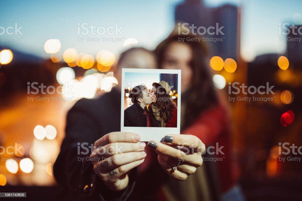 Jovem casal apresentando retrato instantâneo para a câmera - foto de acervo