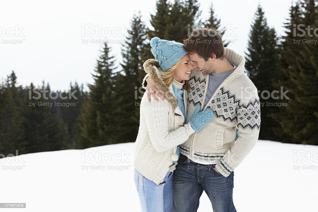 Young couple side hugging in alpine snow scene stock photo