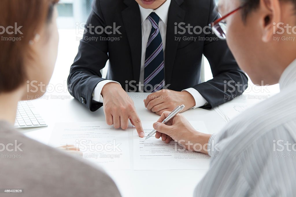 Young couple signing renting contract with real estate agent stock photo