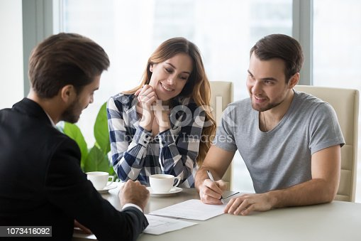 istock Young couple signs contract with realtor, banker 1073416092
