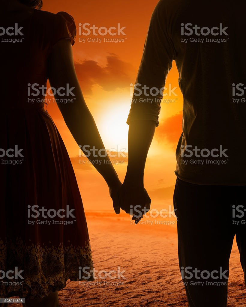 Young couple silhouette on a beach stock photo