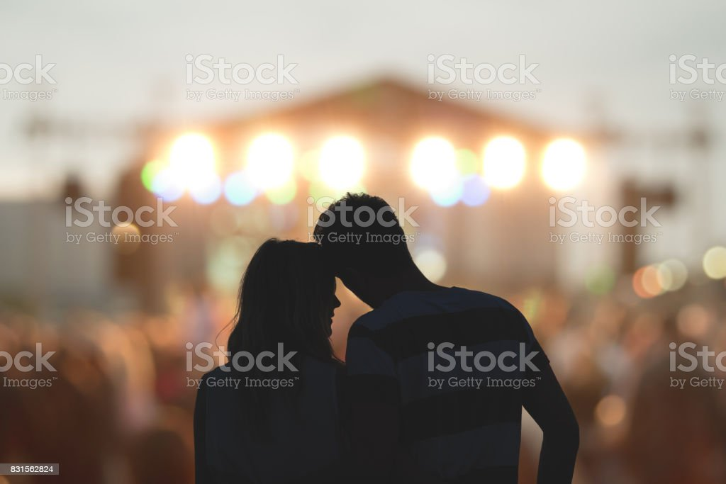 Young couple silhouettes enjoying on the concert. stock photo