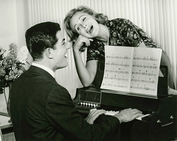 young couple singing, man playing piano, (b&w) - 1940s style stock photos and pictures