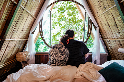 Young Couple Sit Close Together Admiring Nature Looking Out Though A Window Of A Rustic Natural Guest House Bedroom Stock Photo - Download Image Now