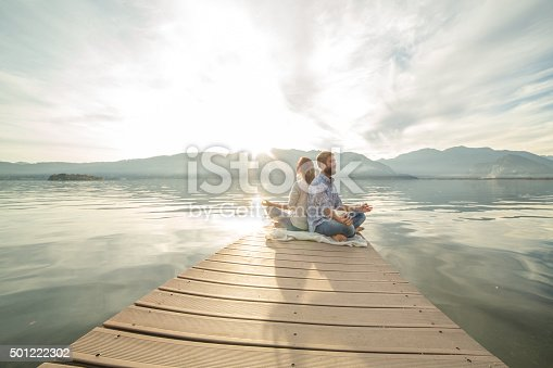 Young couple sits on a jetty above the lake, exercises yoga. Beautiful Autumn day in Italy.