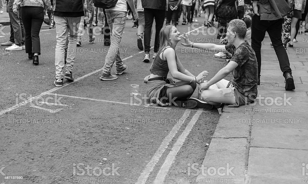 Young couple sitting and drinking in middle of the road stock photo
