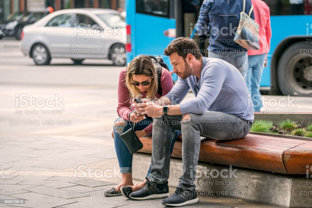 Young couple sitting and looking at their mobile phones. royalty-free stock photo