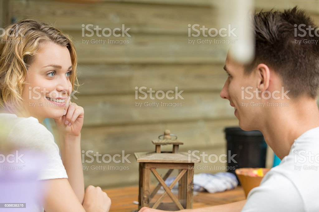 young couple sitting at a table and speaking - foto de acervo