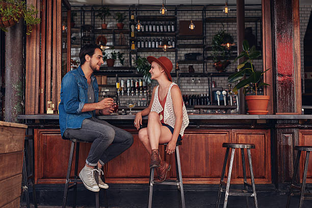 Young couple sitting at cafe counter Shot of young couple sitting at cafe counter. Young man and woman at coffee shop. stool stock pictures, royalty-free photos & images