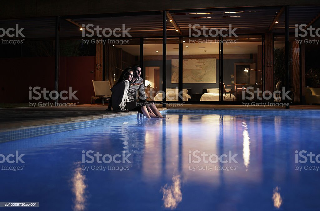 Young couple sitting at edge of pool at night royalty-free stock photo